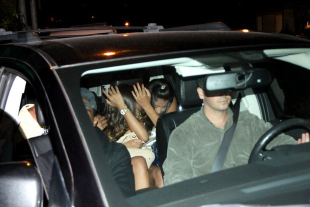 Justin Bieber, in a sheet, with sex slaves. Photo creditt: Francisco Silva/Agnews, via Globo (link)